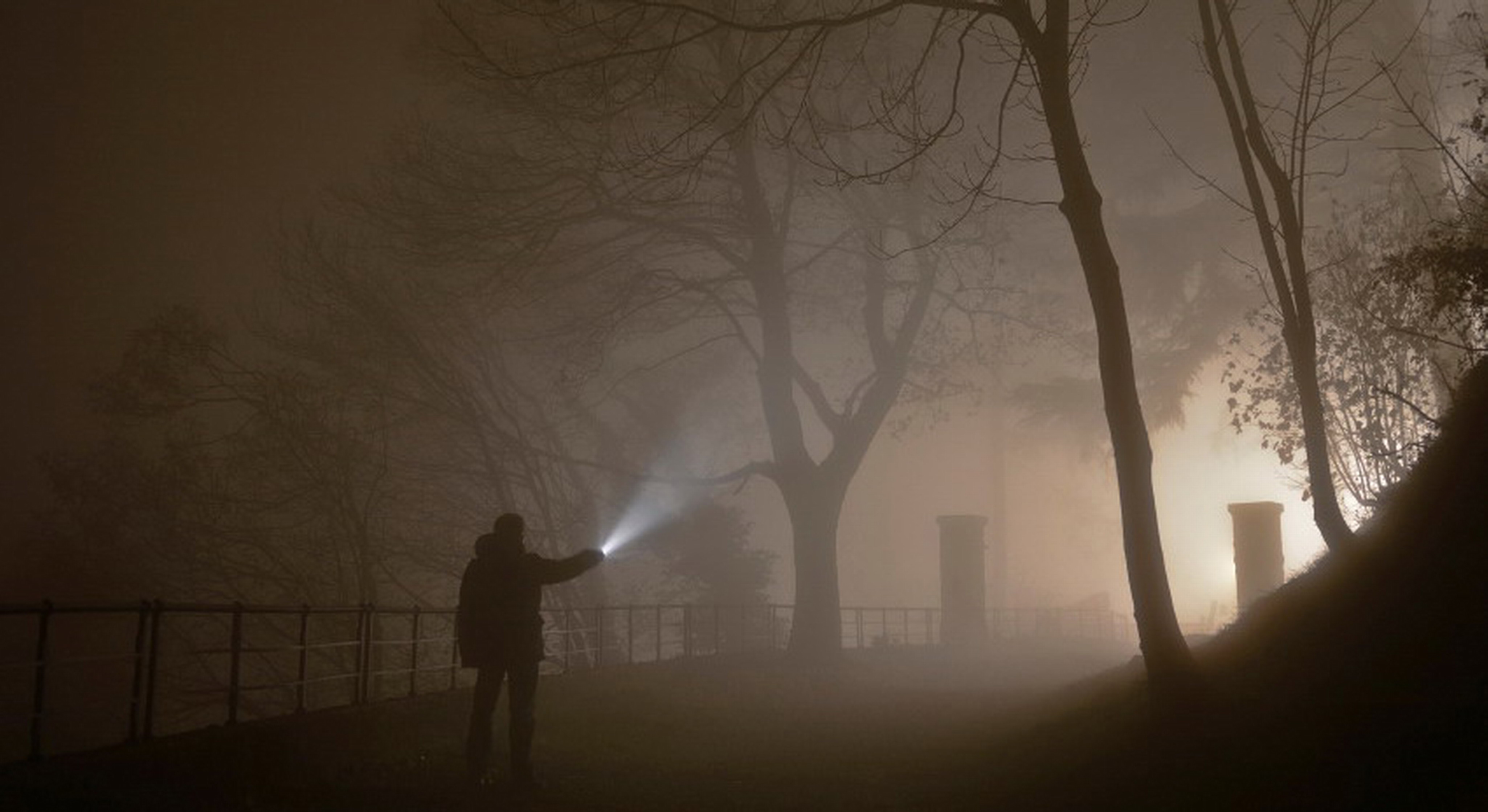 a man in the forest on a foggy night